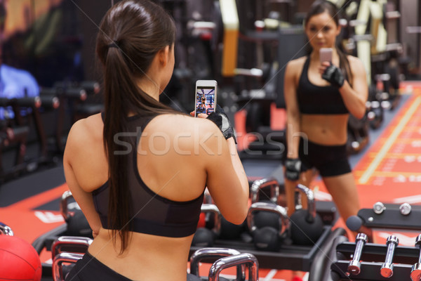 woman with smartphone taking mirror selfie in gym Stock photo © dolgachov