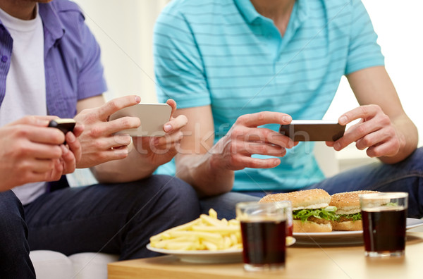 close up of friends with smartphone picturing food Stock photo © dolgachov