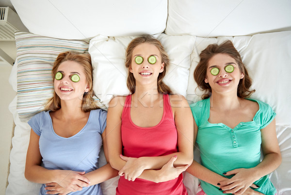 happy young women with cucumber mask lying in bed Stock photo © dolgachov