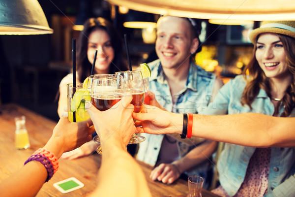 happy friends clinking glasses at bar or pub Stock photo © dolgachov