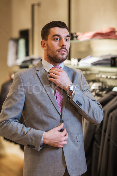young man trying suit on in clothing store Stock photo © dolgachov