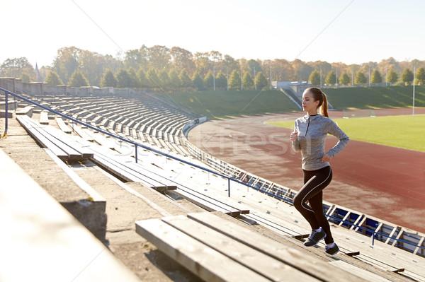 Gelukkig jonge vrouw lopen naar boven stadion fitness Stockfoto © dolgachov