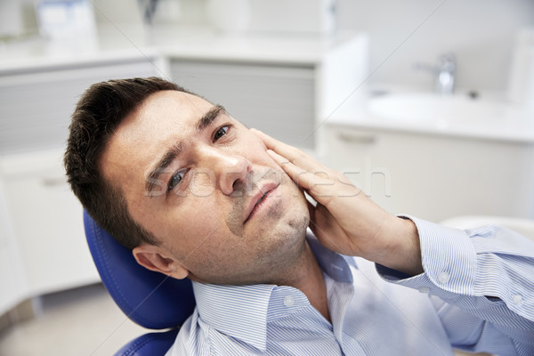 man having toothache and sitting on dental chair Stock photo © dolgachov