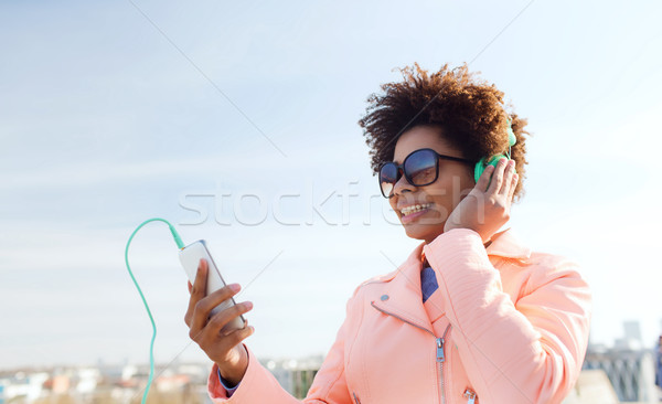 happy young woman with smartphone and headphones Stock photo © dolgachov