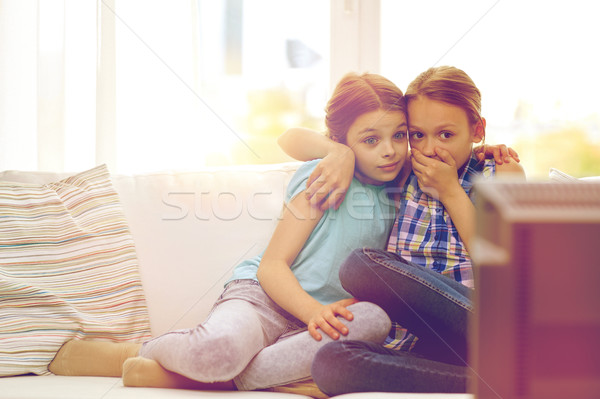 scared little girls watching horror on tv at home Stock photo © dolgachov