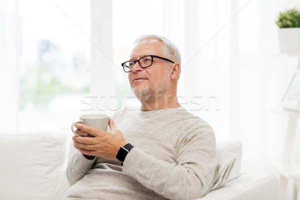 happy senior man with cup of tea at home Stock photo © dolgachov