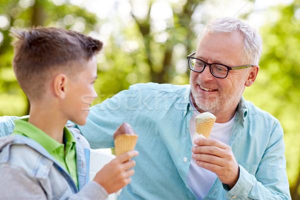 old man and boy eating ice cream at summer park Stock photo © dolgachov