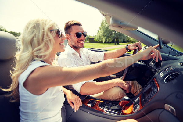 happy couple using gps navigator in cabriolet car Stock photo © dolgachov