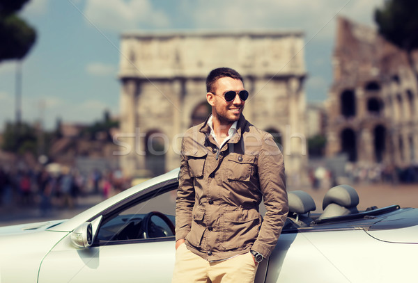 happy man driving cabriolet car over city of rome Stock photo © dolgachov