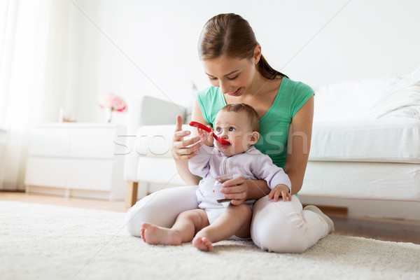 Stock photo: mother with spoon feeding little baby at home