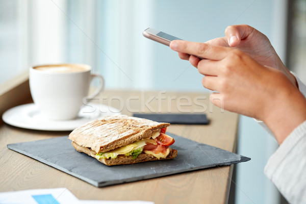 Stock photo: panini sandwich and woman with smartphone at cafe
