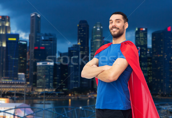 happy man in red superhero cape over night city Stock photo © dolgachov