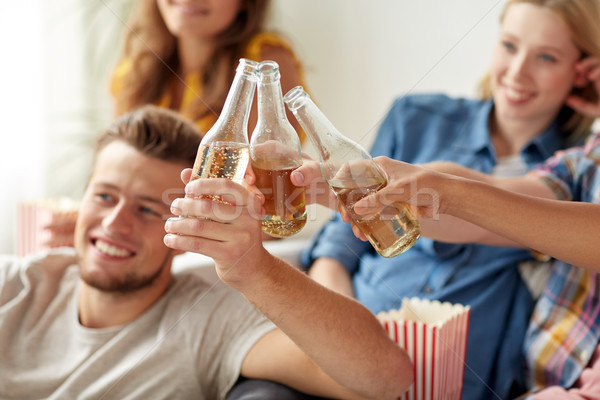 Stock photo: happy friends clinking beer bottles at home party