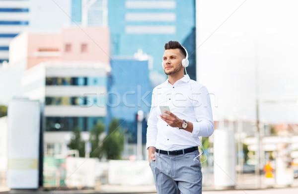 man with headphones and smartphone listening music Stock photo © dolgachov