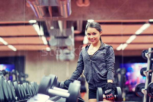 Stock photo: smiling young woman choosing dumbbells in gym