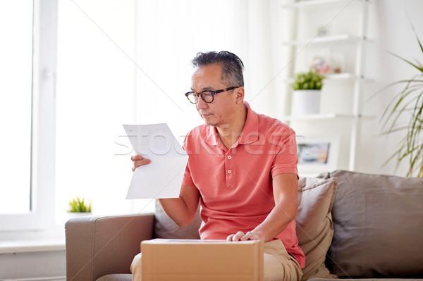 man with parcel box reading invoice at home Stock photo © dolgachov