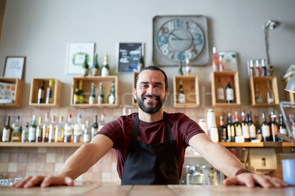 Stock photo: happy man or waiter at bar or coffee shop