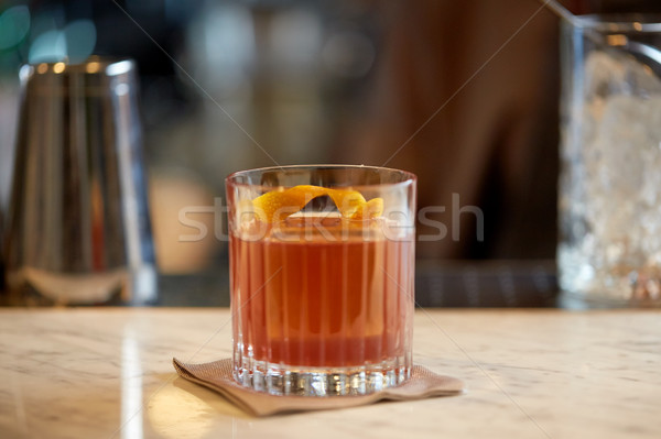 glass of cocktail with orange peel at bar Stock photo © dolgachov