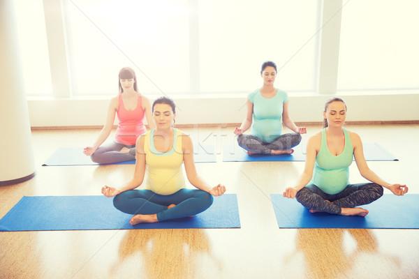 Stock photo: happy pregnant women exercising yoga in gym