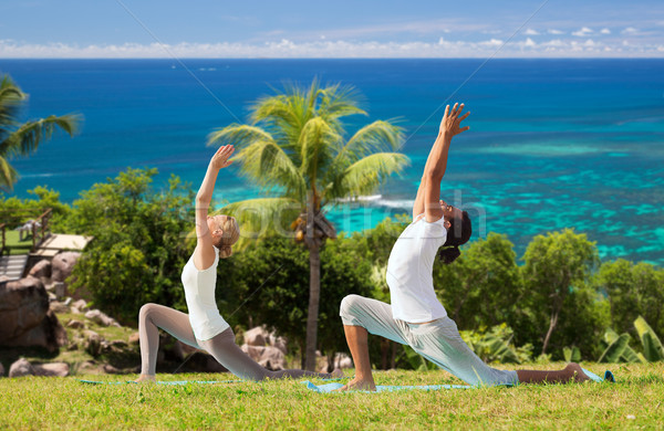 couple making yoga in low lunge pose outdoors Stock photo © dolgachov