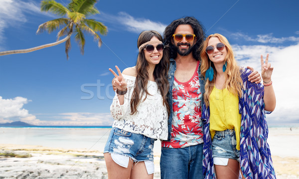 happy hippie friends showing peace on summer beach Stock photo © dolgachov