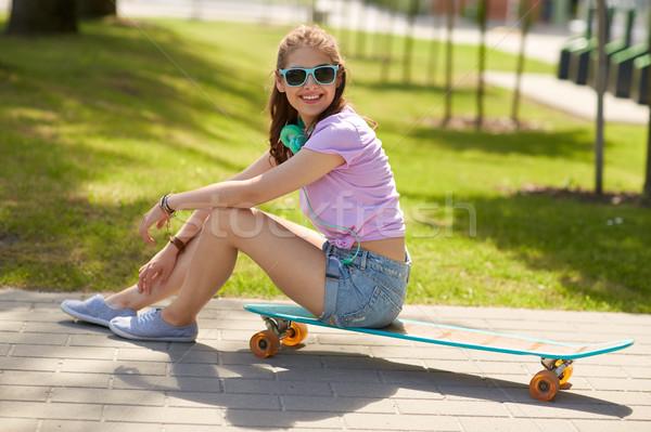 happy teenage girl with headphones and longboard Stock photo © dolgachov