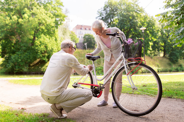 happy senior couple with bicycle at summer park Stock photo © dolgachov