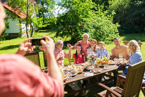 Stock photo: happy family photographing by smartphone in summer