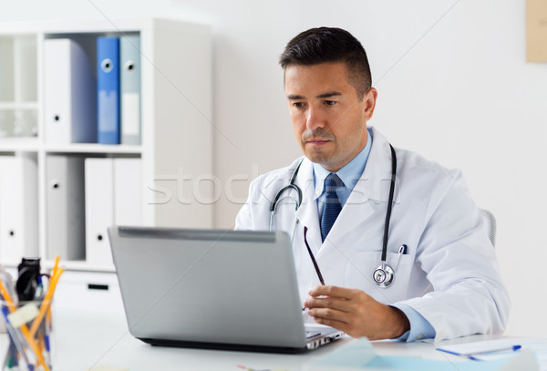 male doctor in white coat with laptop at hospital Stock photo © dolgachov