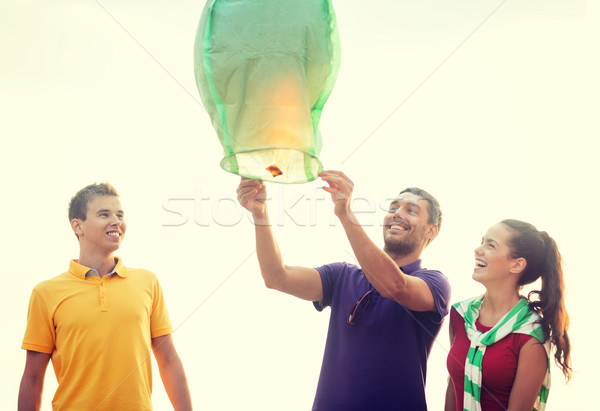 friends with chinese sky lanterns on the beach Stock photo © dolgachov