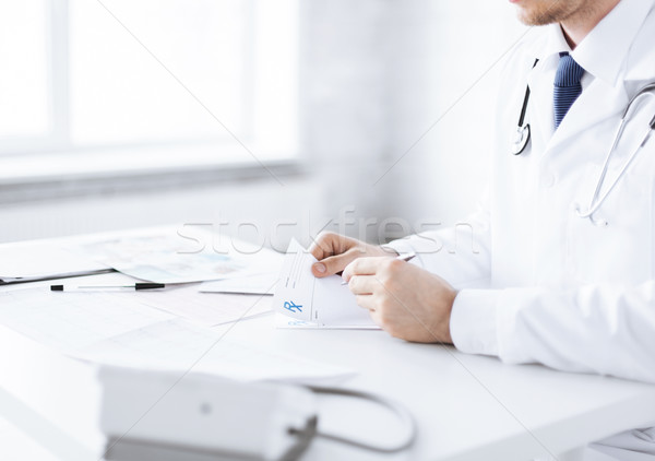 Doctor de sexo masculino escrito prescripción papel familia Foto stock © dolgachov