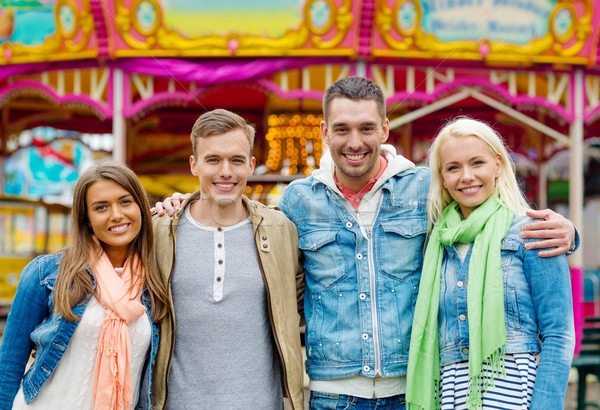 group of smiling friends in amusement park Stock photo © dolgachov