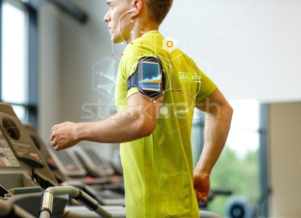 Férfi okostelefon testmozgás futópad tornaterem sport Stock fotó © dolgachov