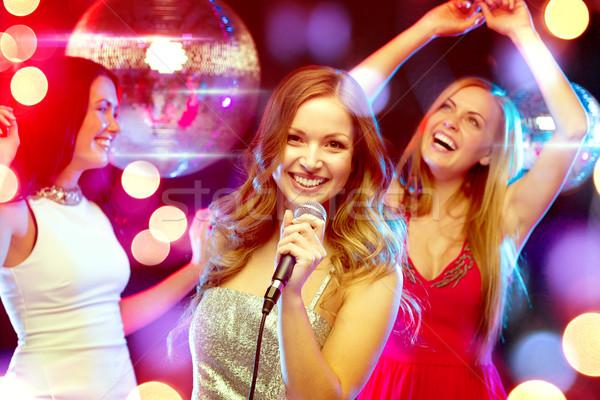Tres sonriendo mujeres baile cantando karaoke Foto stock © dolgachov