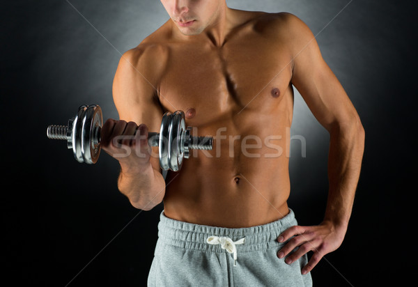 close up of young man with dumbbell Stock photo © dolgachov