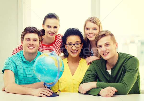 five smiling student with earth globe at school Stock photo © dolgachov