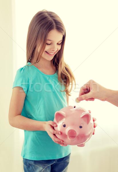 smiling little girl holding piggy bank Stock photo © dolgachov