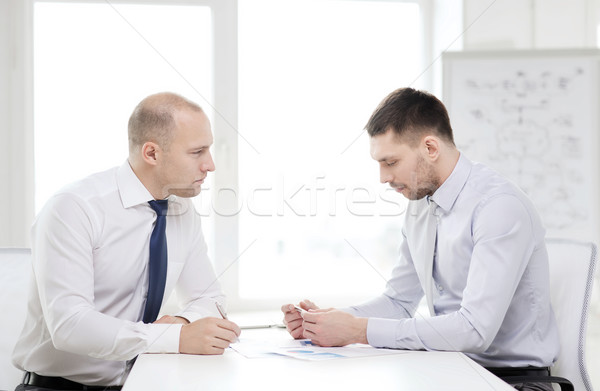 two serious businessman with papers in office Stock photo © dolgachov