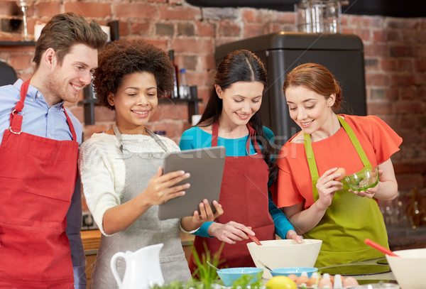 happy friends with tablet pc cooking in kitchen Stock photo © dolgachov