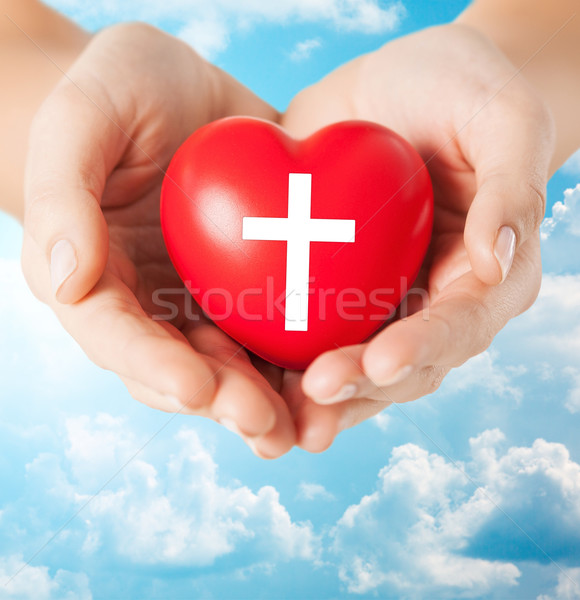 close up of hands holding heart with cross symbol Stock photo © dolgachov