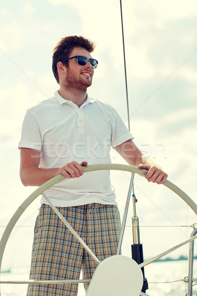 young man in sunglasses steering wheel on yacht Stock photo © dolgachov