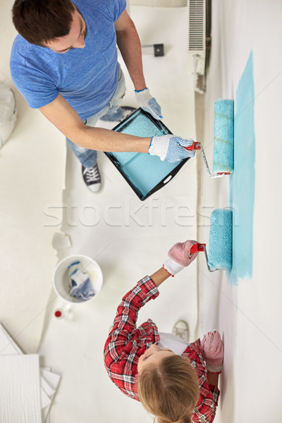 couple with paint rollers painting wall at home Stock photo © dolgachov