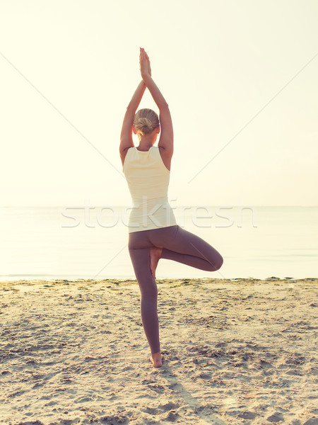 Stock photo: woman making yoga exercises outdoors from back