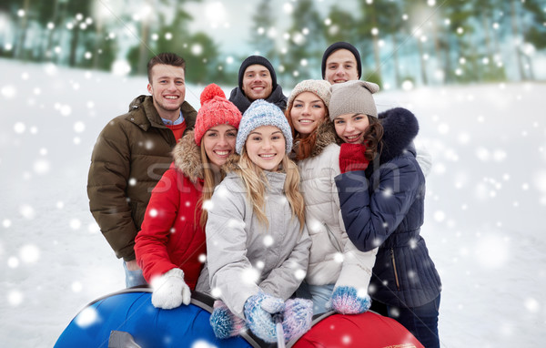 smiling friends with snow tubes and selfie stick Stock photo © dolgachov