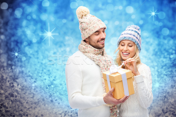 smiling couple in winter clothes with gift box Stock photo © dolgachov