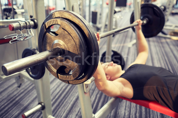 Stock photo: close up of man flexing biceps with barbell in gym