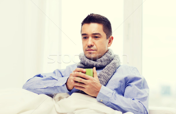 ill man with flu drinking hot tea from cup at home Stock photo © dolgachov