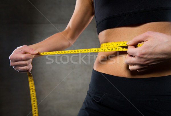close up of woman measuring waist by tape in gym Stock photo © dolgachov