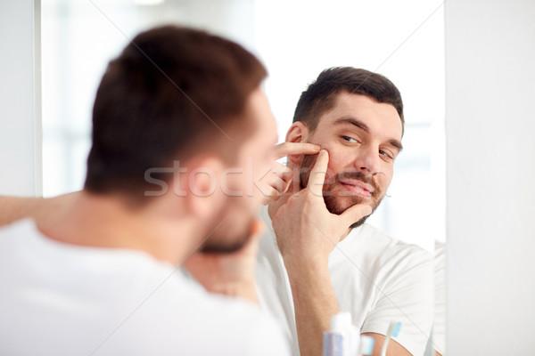 Uomo brufolo bagno specchio bellezza igiene Foto d'archivio © dolgachov