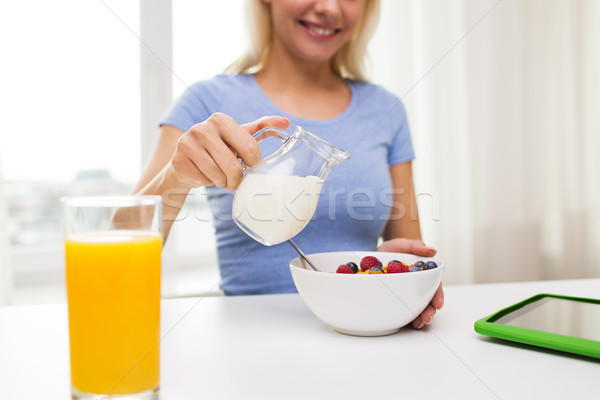 close up of woman with milk jug eating breakfast Stock photo © dolgachov
